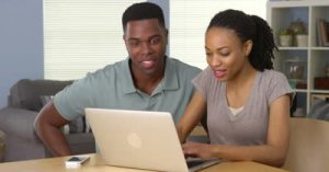 stock-footage-young-black-man-and-woman-using-laptop-together-at-desk